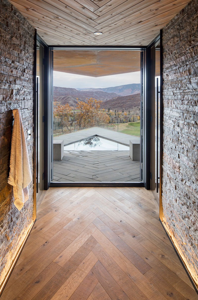 In this modern mountain house, wood installed in a herringbone pattern features on the ceiling and on the floor, while a large floor-to-ceiling picture window frames the view of the mountains. #Windows #Flooring #Ceiling