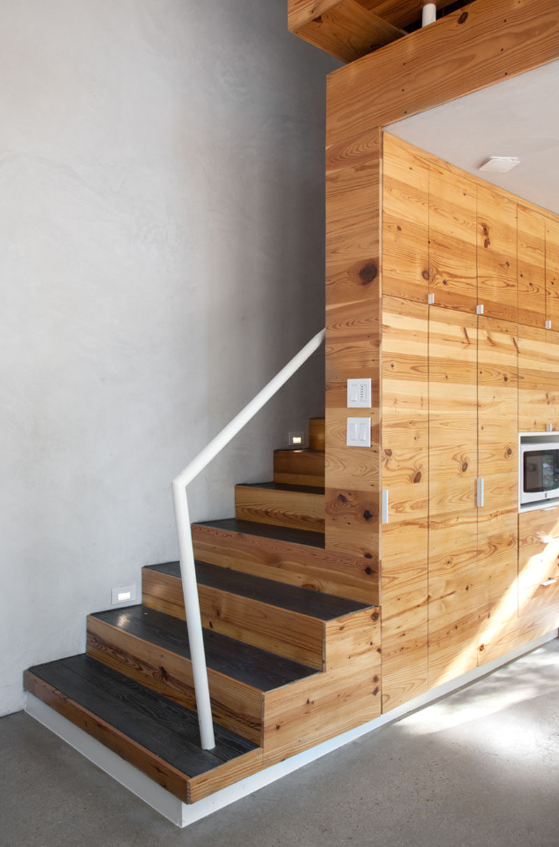 Wood stairs with charred wood treads and a white handrail lead to the second floor of this modern apartment. #WoodCabinetry #Stairs #StairDesign