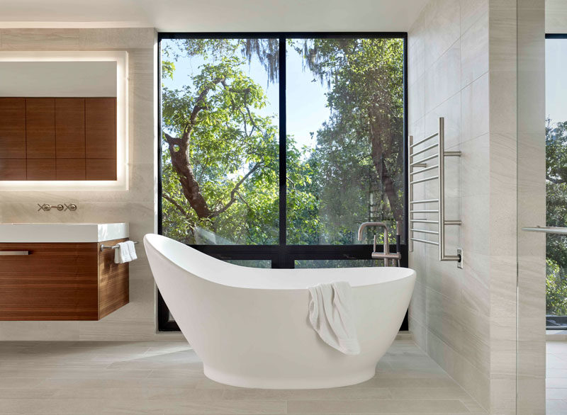 In this modern master bathroom, a curved freestanding bathtub is positioned in front of the windows to take in the tree views. #MasterBathroom #BathroomDesign