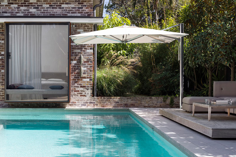 This Australian house has a swimming pool that meets the house and a deck that's located in the shade of the trees. #SwimmingPool