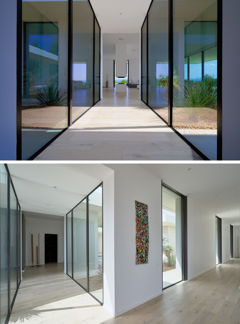 This modern hallway has floor-to-ceiling windows that provide a view of the garden and plenty of natural light. #Hallway #FloorToCeilingWindows