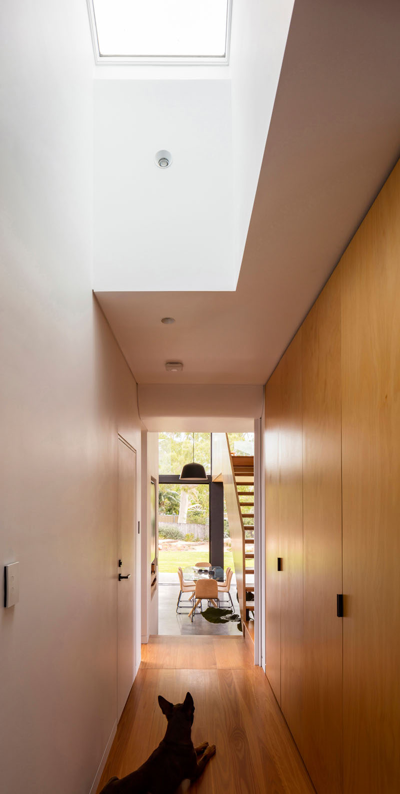 This house features a hallway lined with wood closets that leads to the new extension, and a skylight adds natural light to the interior. #Hallway #InteriorDesign #Skylight