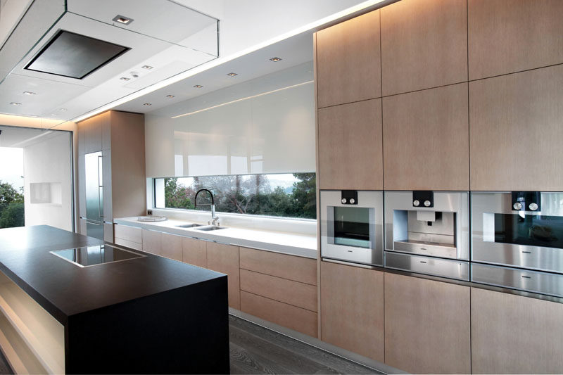 In this modern kitchen, light minimalist wood cabinets have been paired with both a white countertop and a black kitchen island. #KitchenDesign #ModernKitchen