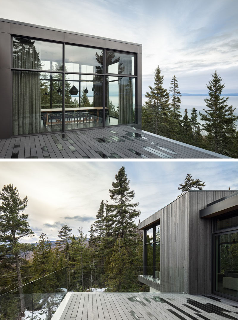 The social areas of this modern house open up to a deck with a glass railing, so that the home owners can enjoy uninterrupted scenic views. #ModernHouse #Deck #Windows