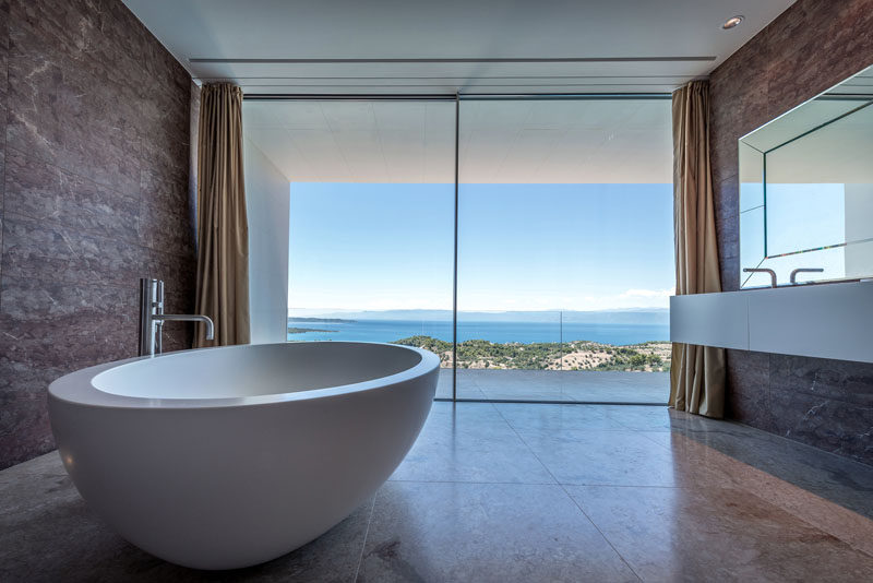 Large floor-to-ceiling windows provide this modern bathroom with a view of the water. #Bathroom #ModernBathroom #Windows