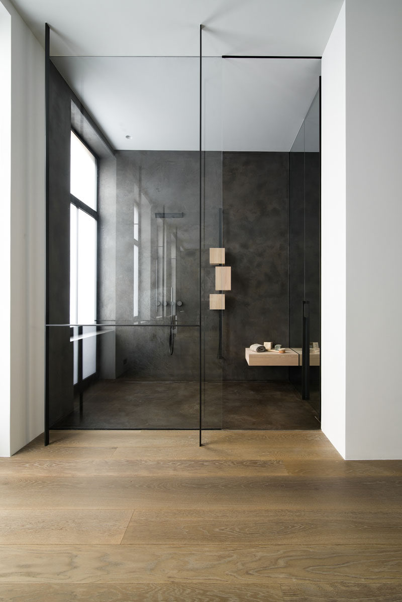 This modern bathroom has wood floors and a walk-in shower that's enclosed behind a glass shower screen. #BathroomDesign #ModernBathroom #ModernShower