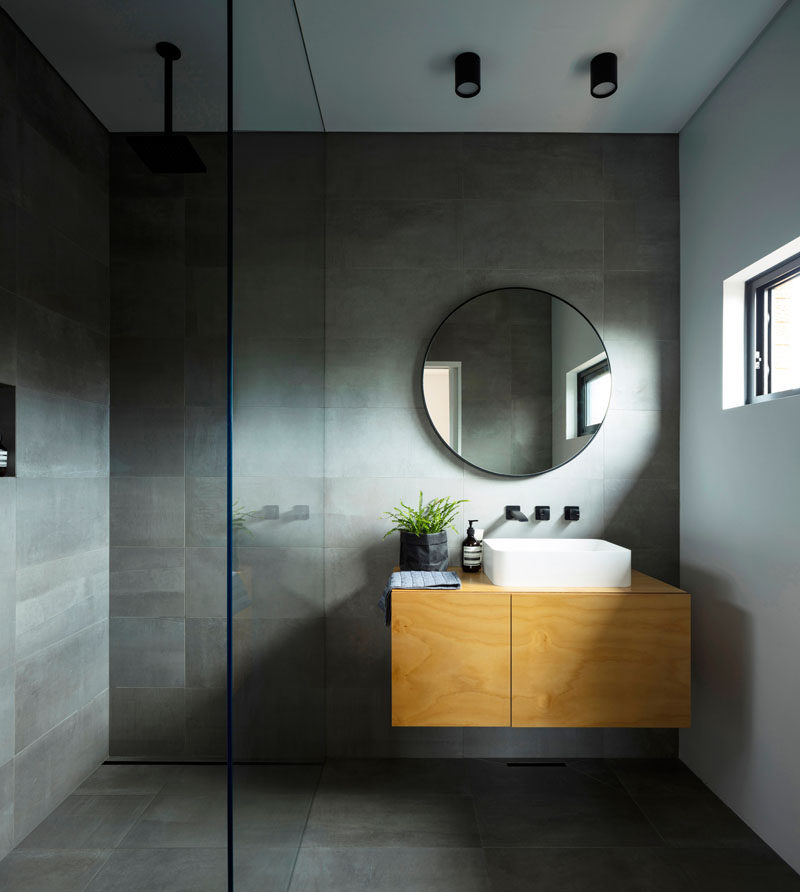 This modern master ensuite bathroom has dark grey tiled walls and floor, a light wood vanity, and a round mirror. #MasterBathroom #BathroomDesign #GreyTiles