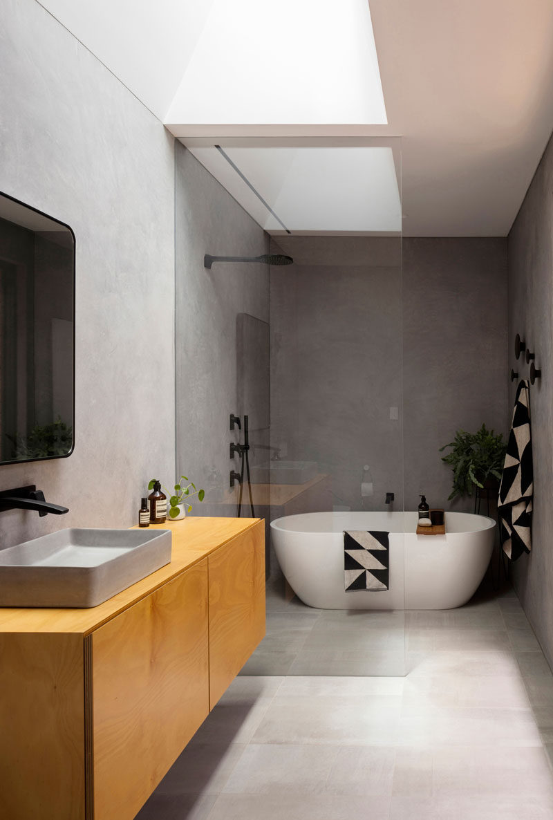 In this modern bathroom, there's a skylight adding natural light, while a glass partition separates the shower and bath from the rest of the room. #ModernBathroom #BathroomDesign #BathroomLayout
