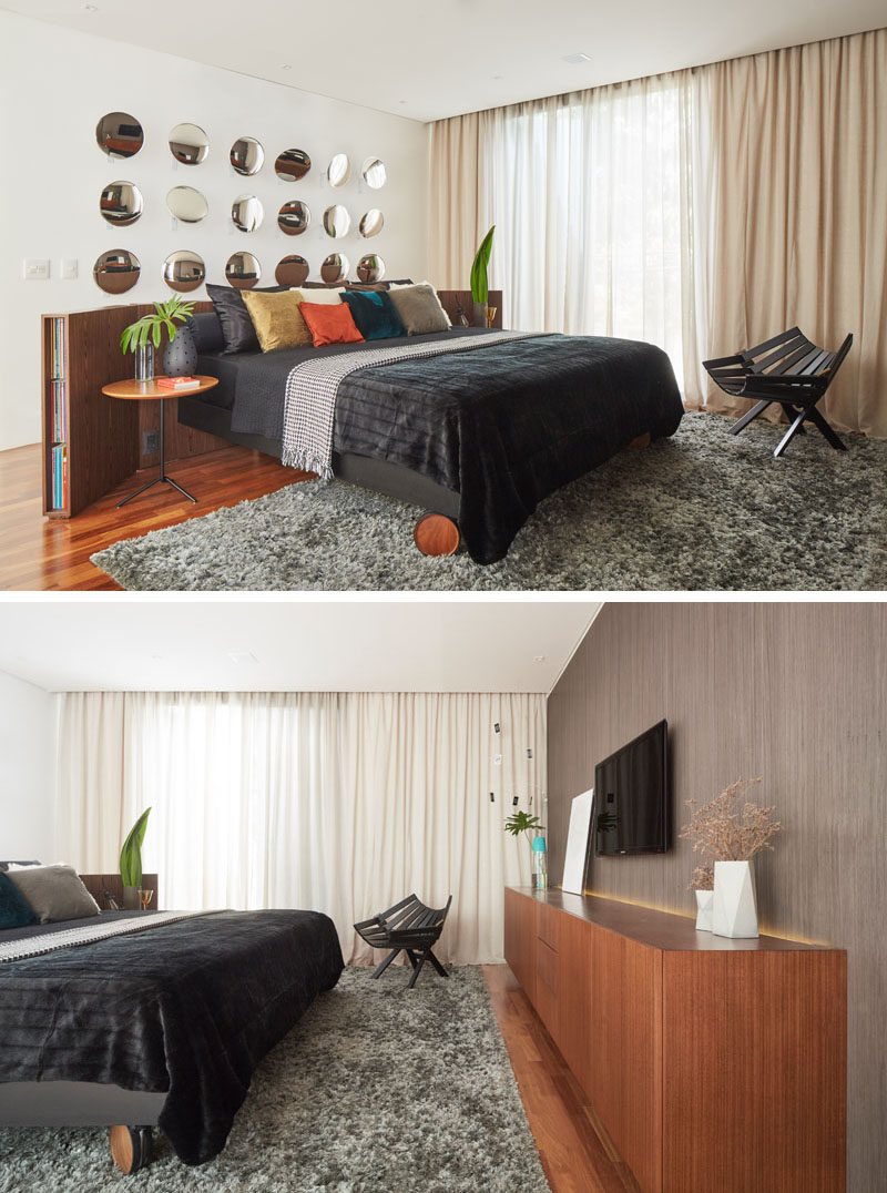 In this modern bedroom, the bed has been placed in the center of the room, with a curved wood headboard. Round mirrors on the wall reflect the sunlight and the cabinetry on the opposite wall. #ModernBedroom