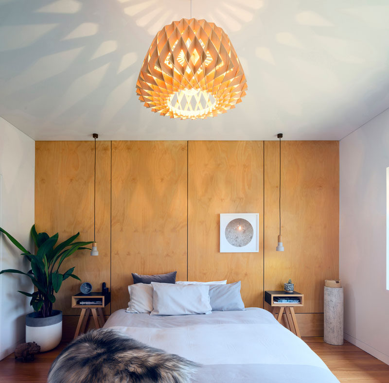In this contemporary master bedroom, wood covers an entire wall and acts as a headboard for the bed. #BedroomDesign #WoodAccentWall