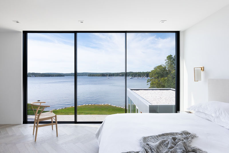 In this modern bedroom, black framed floor-to-ceiling windows perfectly highlight the water view. #Windows #Bedroom