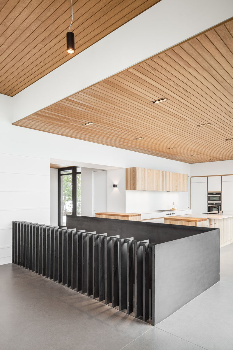 Separating the living room from the kitchen in this modern house, is the steel guardrail for the stairs that lead to the bedrooms and bathrooms on the lower level #Guardrail #InteriorDesign #Stairs