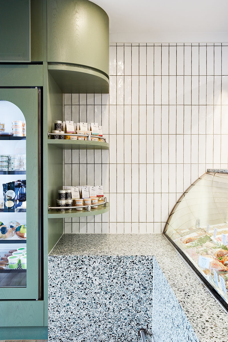 A calming soft green and white color palette has been used throughout the interior, while wood floors define the retail area of this modern butcher and add a natural element. #ModernButcher #ModernRetail #Shelving #RetailDesign #InteriorDesign