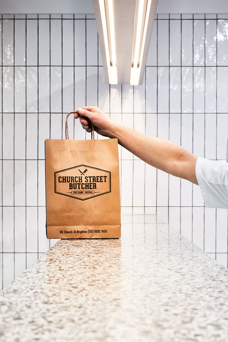 In this modern butcher, white rectangular tiles with dark grout cover the walls, and the service counter is made from a Terrazzo slab. #ModernRetail #ModernButcher #InteriorDesign #RetailDesign