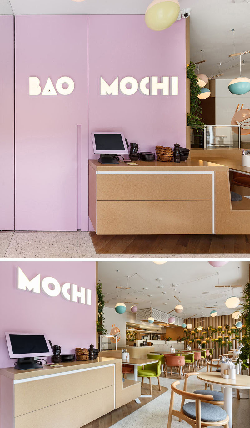 A soft purple accent wall with the restaurants logo greets customers as they arrive. #RestaurantDesign #Signage #InteriorDesign