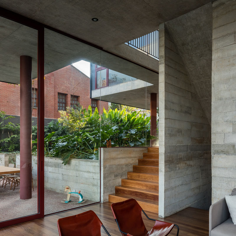Exposed board formed concrete walls line the stairs that connect the various floors of this modern house. #ConcreteWalls #GlassWalls #Architecture