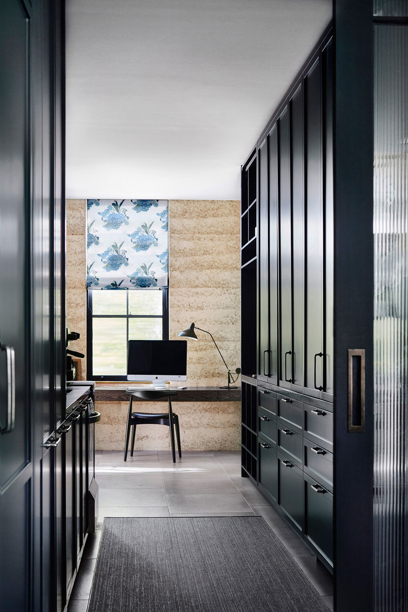 In this modern house, dark cabinetry lines a hallway that leads to a home office, with a desk positioned in front of the window. #DarkCabinets #HomeOffice