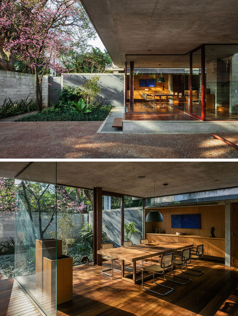 Located at the front of this modern house is the dining room and kitchen, both of which are slightly elevated relative to the sidewalk. Glass walls allow an abundance of natural light to filter through to the interior, and provide views of the gardens. #DiningRoom #GlassWalls