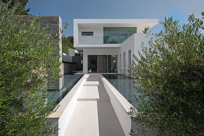 Water features line the path to the front door, while stone accents and plants contrast the white exterior of the house. #Landscaping #WaterFeature #ModernArchitecture