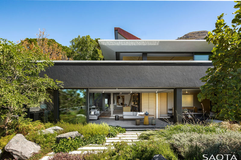 SAOTA have designed a modern family home in Cape Town, South Africa, that sits below Lion's Head, and has sweeping views of the surrounding area. #ModernHouse #HouseDesign #Landscaping