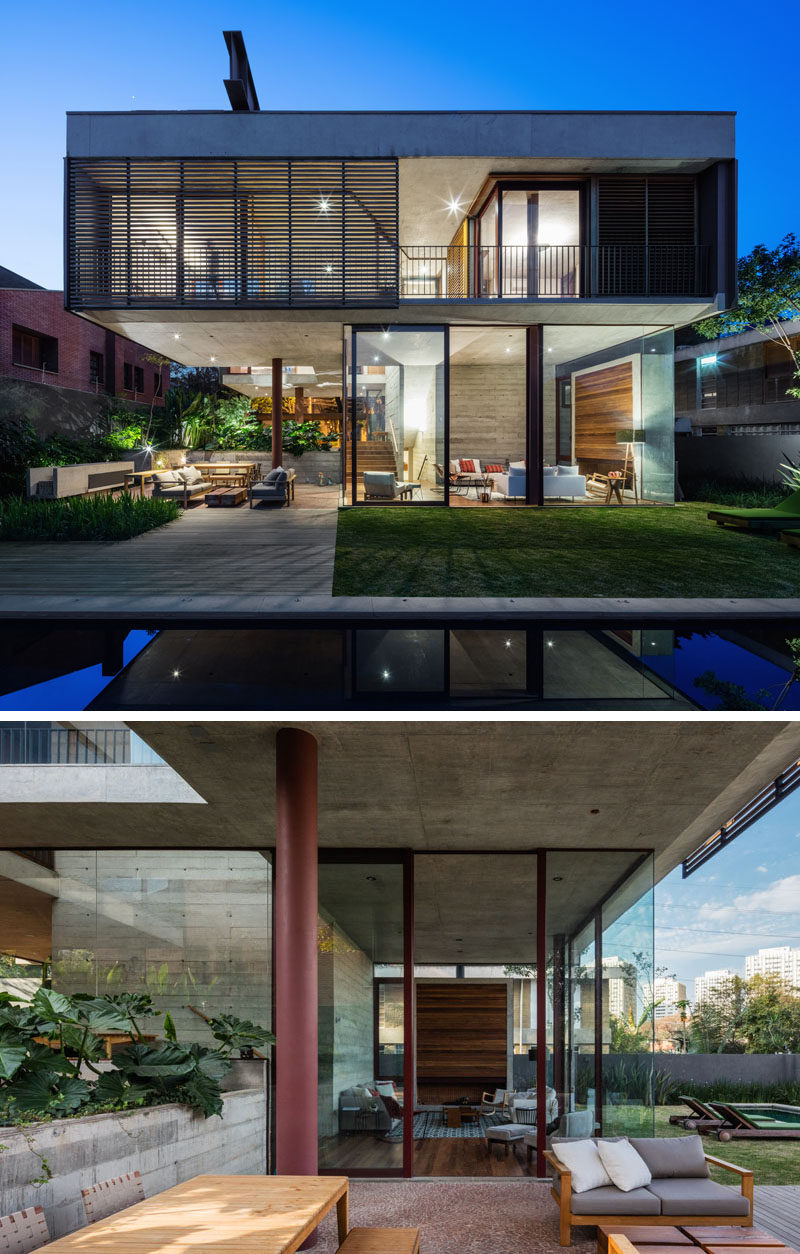 The living room of this modern house opens to the backyard, and there's a cantilevered section of the upper floor that provides shade for the outdoor dining and lounge area. #ModernLivingRoom #ModernHouse #OutdoorLivingRoom