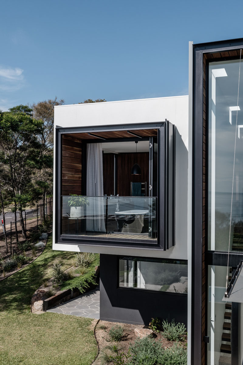 The master bathroom of this modern house opens up to a private balcony that's surrounded by wood. #ModernHouse #Balcony