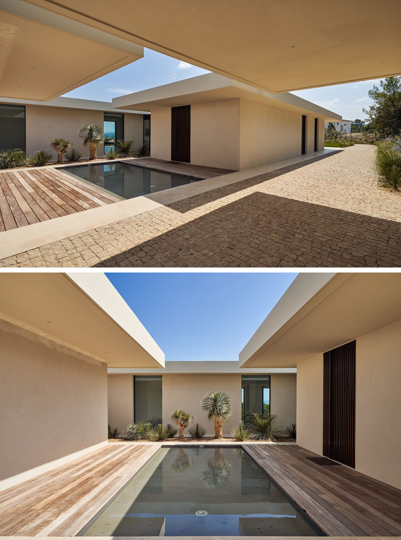Opposite the carport of this modern house, there's a water feature and a strip of landscaping against the house. #WaterFeature #Landscaping #Architecture