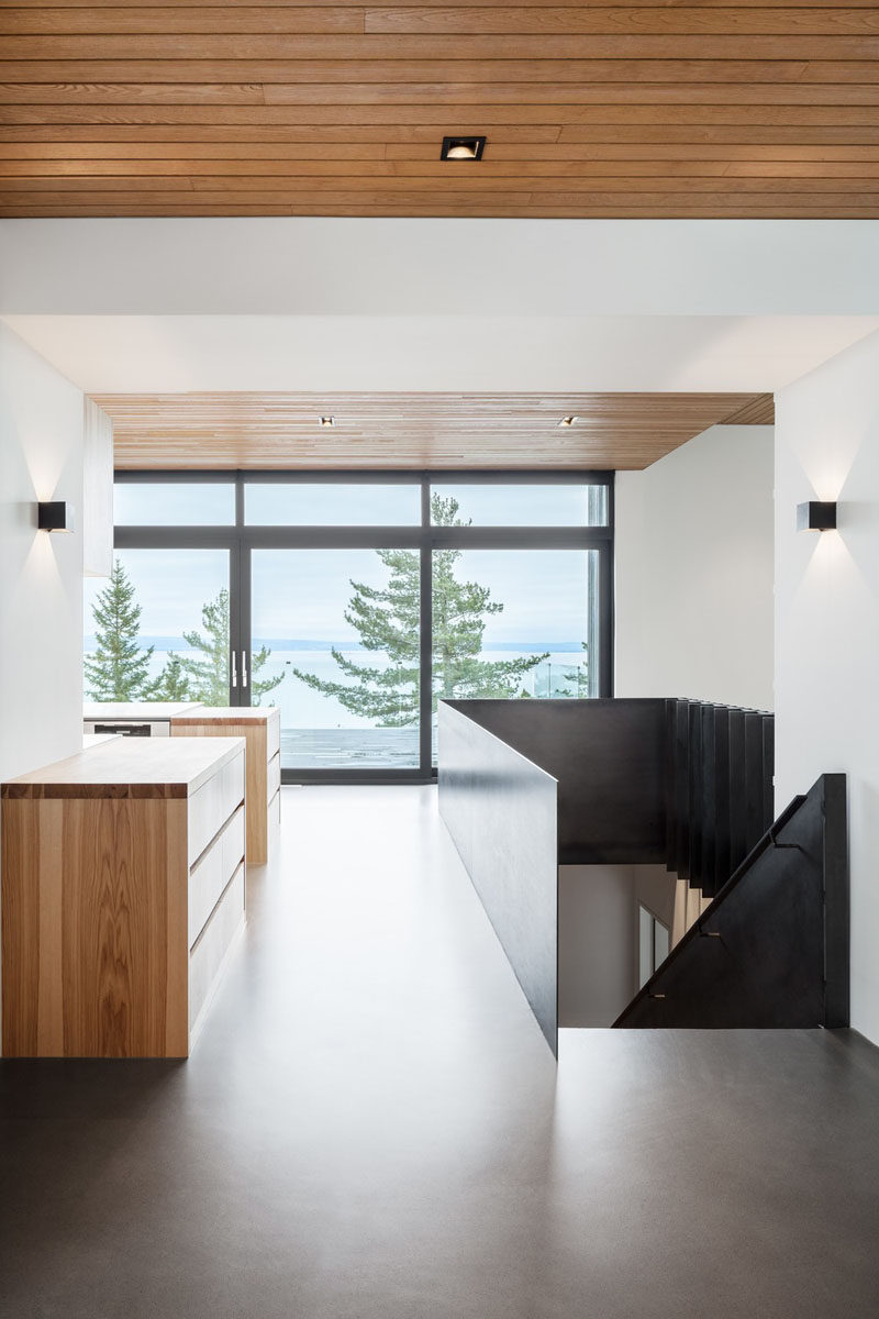 The entryway of this modern house has concrete floors and wood ceilings, and opens up to the main floor with the living room, kitchen, and dining room. #Entryway #WoodCeiling #ConcreteFloors