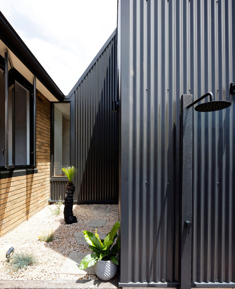 A modern black house extension was added to a brick house in Australia. #ModernArchitecture #OutdoorShower