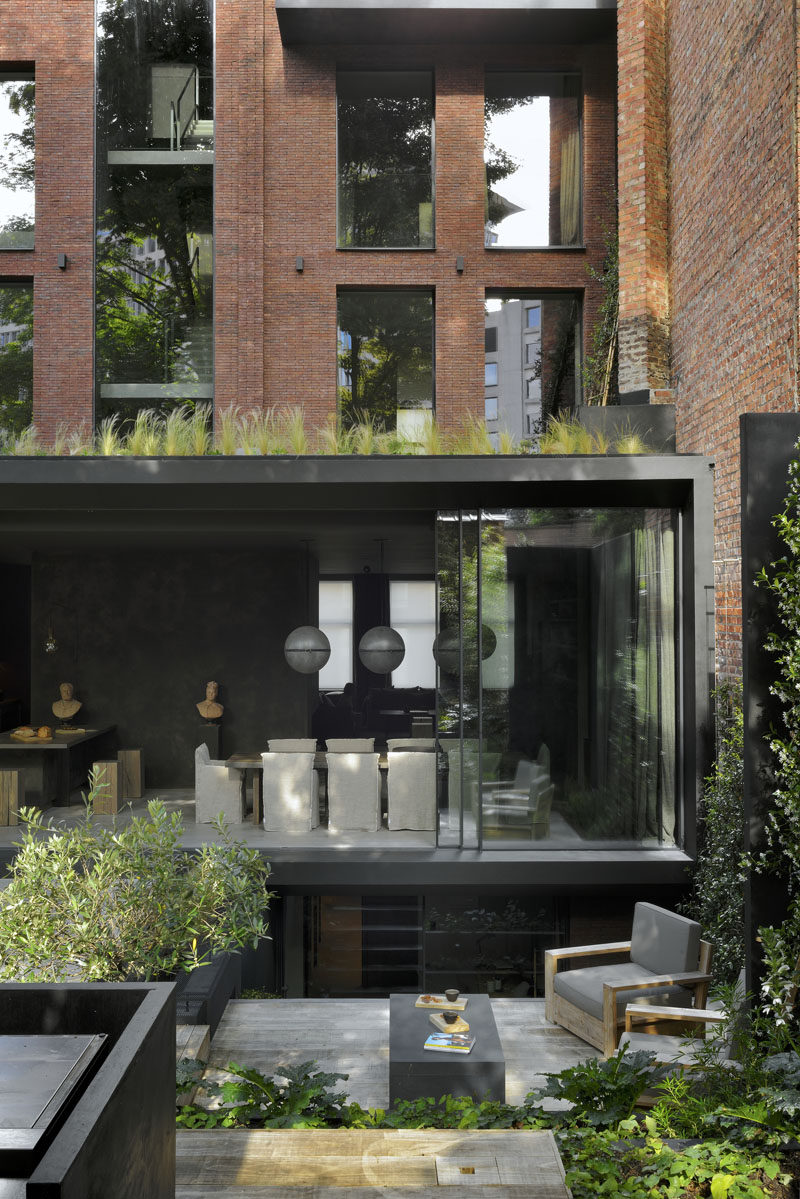 The renovation of this brick home allowed for a new extension to the back of the house, which has large sliding glass doors that open to the updated rear garden. #ModernArchitecture #Landscaping