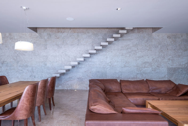 This modern house has floating stairs, located against the wall, that lead to the upper floor of the home. #Stairs #StairDesign #FloatingStairs