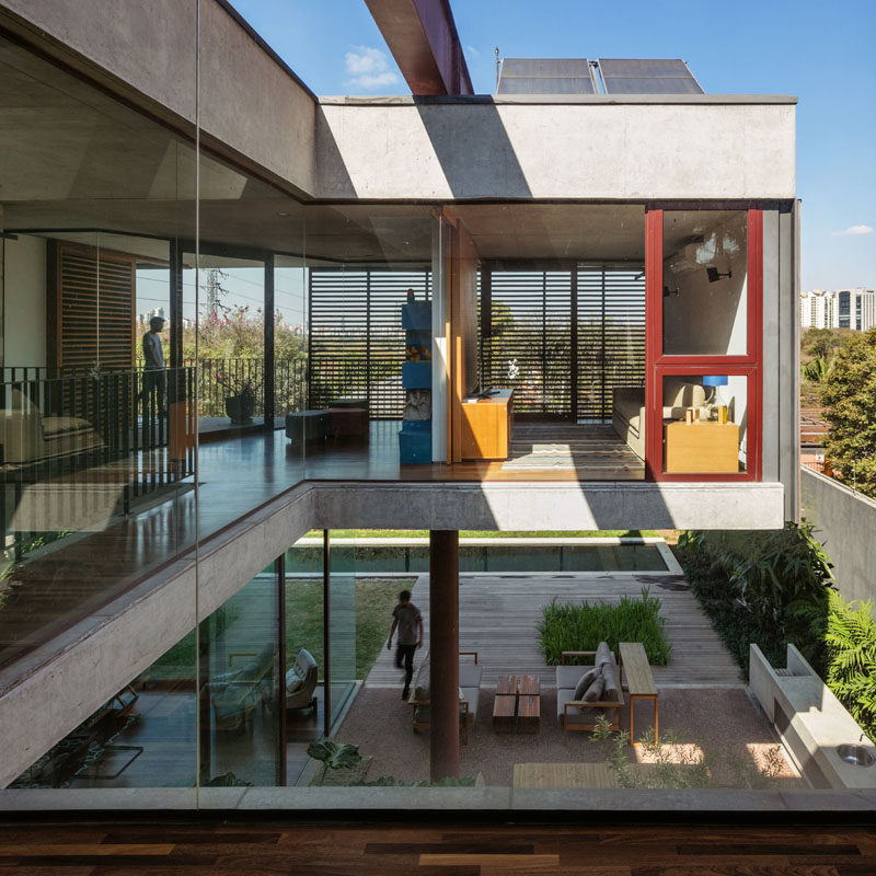 The top floor of this modern house has glass walls and a balcony that side garden, backyard, and swimming pool. #GlassWalls #ModernHouse