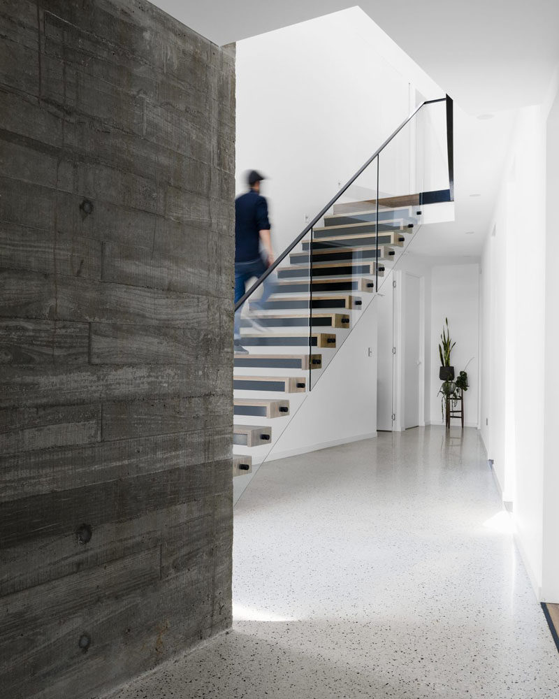 Stairs with a glass and steel railing connect the various levels of this modern house, #Stairs #Concrete