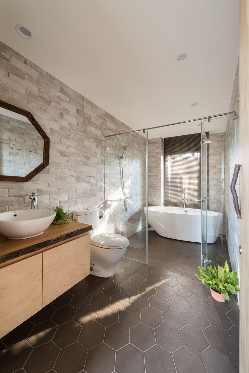In this modern bathroom, a glass partition separates the shower and freestanding bath from the toilet and vanity area. #BathroomDesign #ModernBathroom