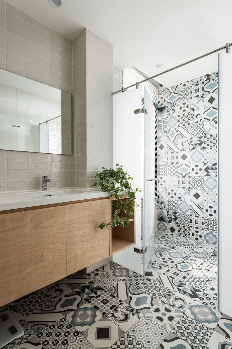 In this modern bathroom, colorful and patterned tiles have been combined with more neutral grey rectangular tiles for a modern appearance. #PatternedTiles #BathroomDesign