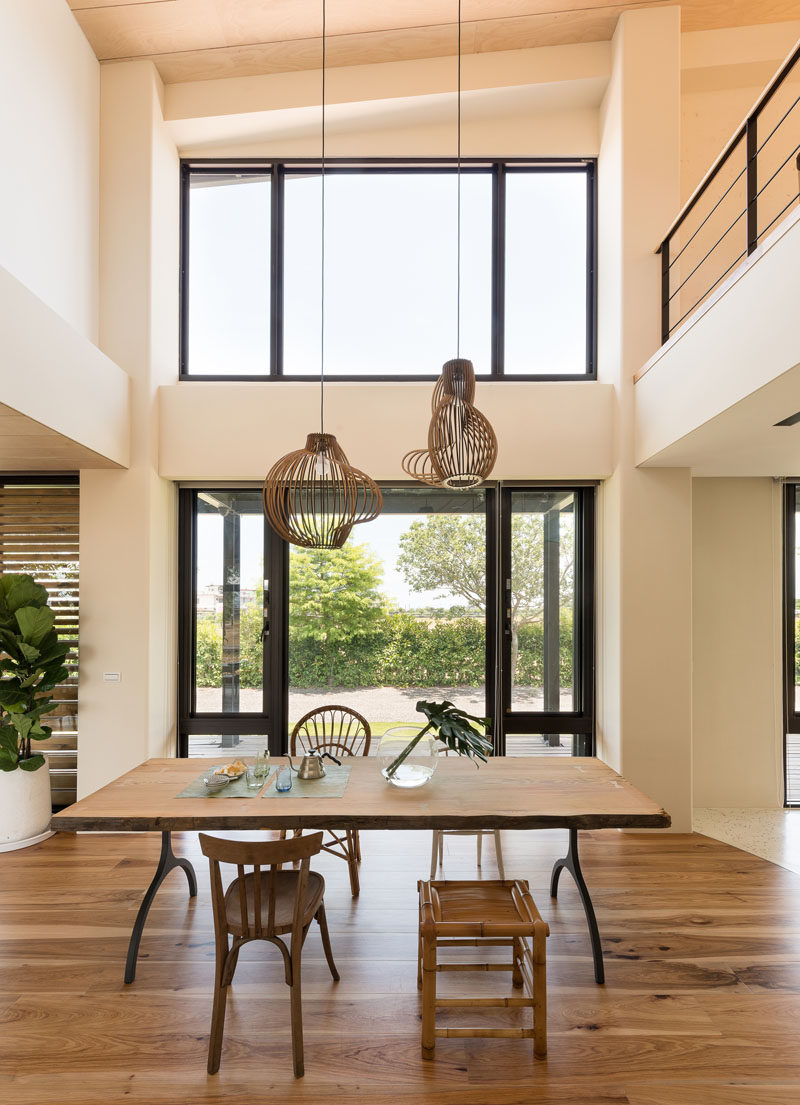 In this open dining area, a simple wood dining table is surrounded by different styles of seating, while two pendant lights hang from the high ceiling. #DiningRoom #InteriorDesign