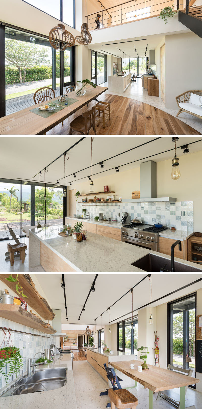 This modern house has kitchen with a long kitchen island that transforms into a casual dining area, while lower cabinets line the wall and raw edge floating shelves sit above the tile backsplash. #KitchenDesign #ModernKitchen