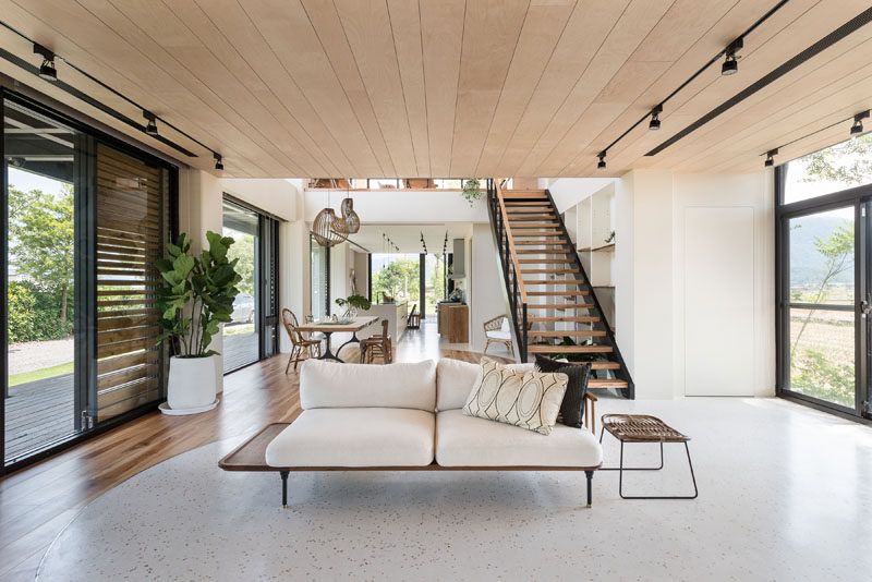 This living room is decorated with minimal furniture, and on either side, windows and sliding glass doors add plenty of natural light. #LivingRoom #InteriorDesign