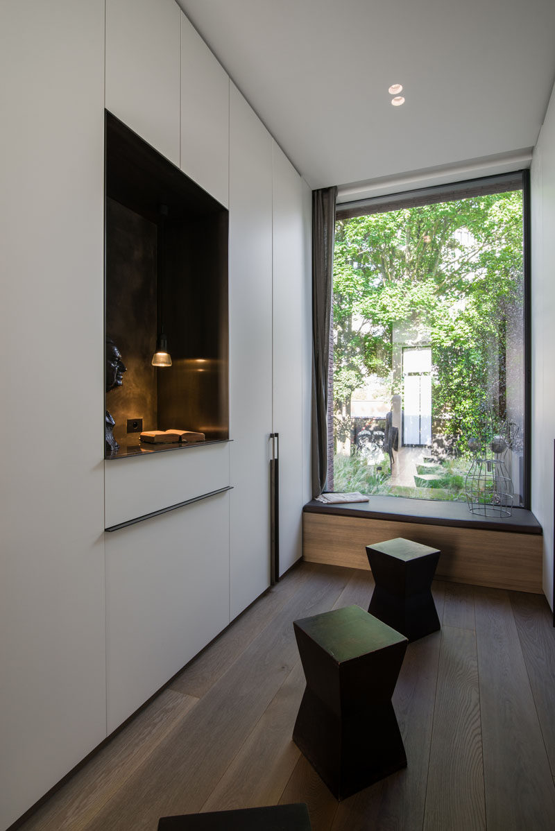 Large windows allow natural light to filter through to the interior of this modern house, and by this window, a simple bench is positioned to take advantage of the garden views. #WindowSeat #Window