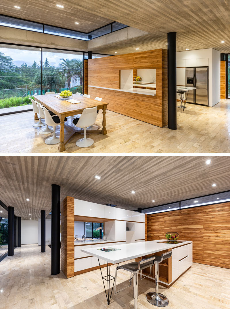 This modern house has a wood partition wall with a pass-through between the kitchen and dining room. #ModernKitchen #DiningRoom #InteriorDesign