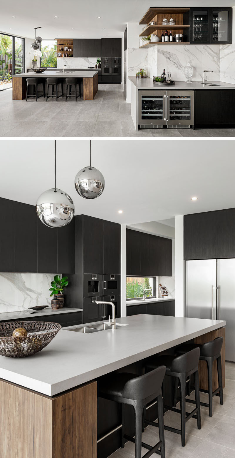 A modern kitchen divided into two areas, has the main kitchen with a large island, while adjacent to it, is a wet bar with storage for glasses, a small sink, and two small built-in fridges.