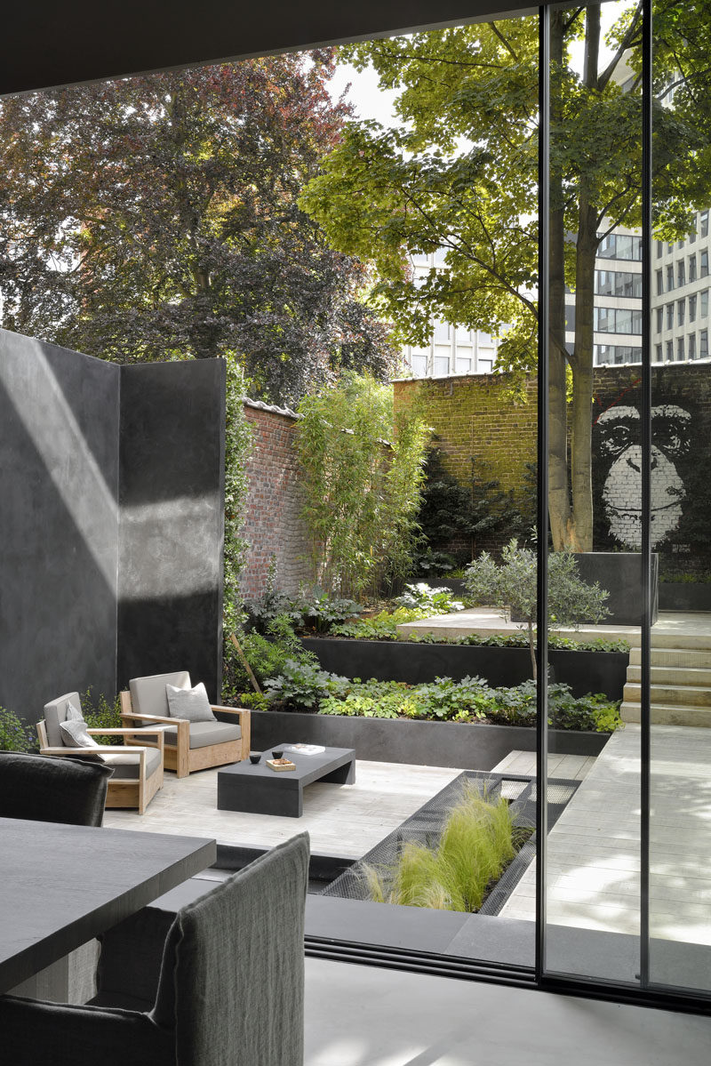 This modern garden has been landscaped with various levels, creating places for the home owners to relax in the lounge, or take in the mural on the back brick wall. #Landscaping #GardenDesign