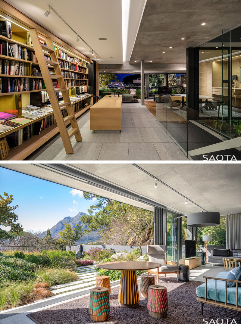 This modern house features a library that has a bookshelf that runs floor-to-ceiling and wall-to-wall, and a rolling library ladder for reaching the high shelves. At the end of the library, there's a lounge that opens to a landscaped garden. #Library #Bookshelf #Lounge #Garden #Landscaping
