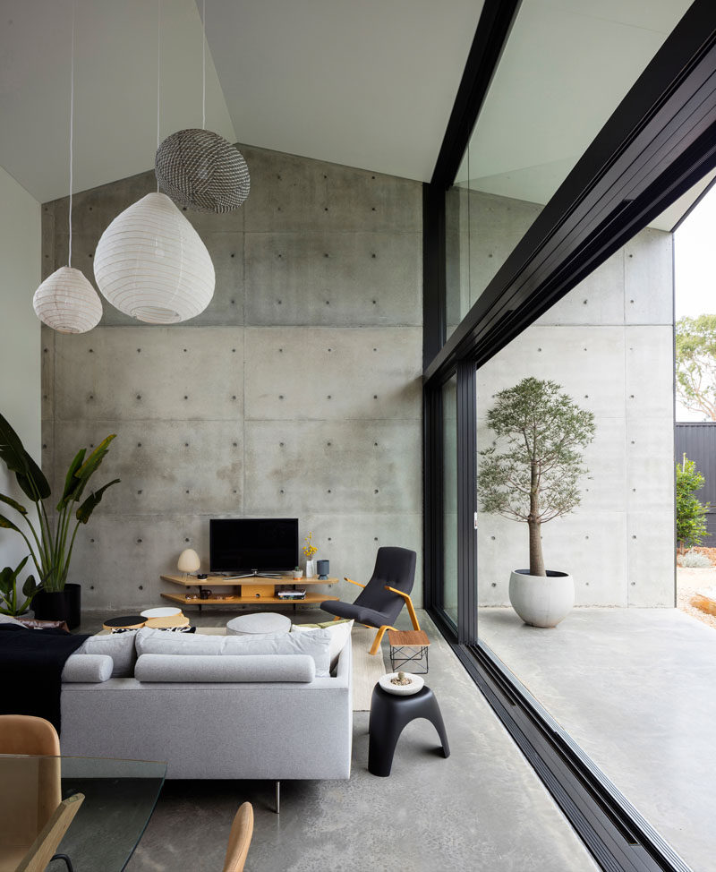 In this modern living room area, a double-height ceiling creates an open feeling, while a large exposed concrete wall continues from the interior to the exterior of the home. #LivingRoom #ConcreteWall