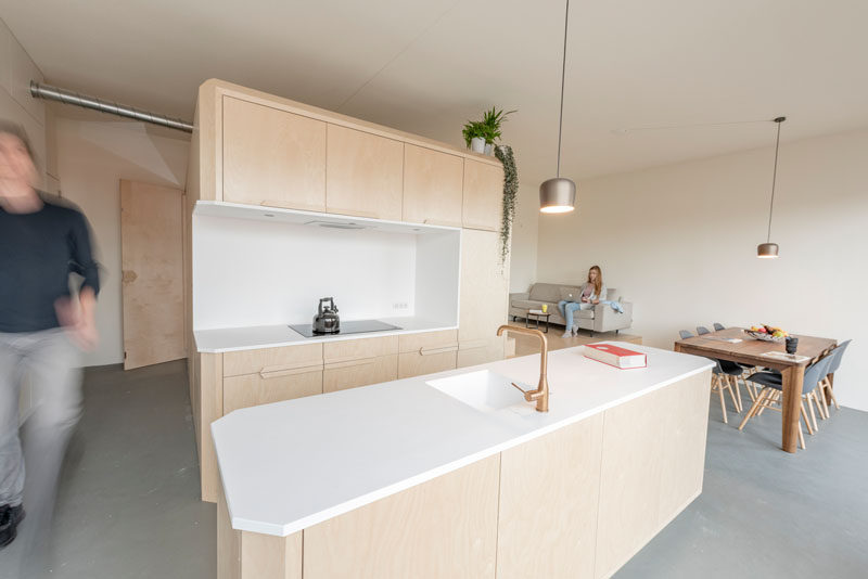 This modern loft apartment has a subtle palette of birch wood and white Corian. There's a bathroom, storage room, kitchen, raised living room, and a lofted bedroom. #InteriorDesign #ApartmentDesign #Loft