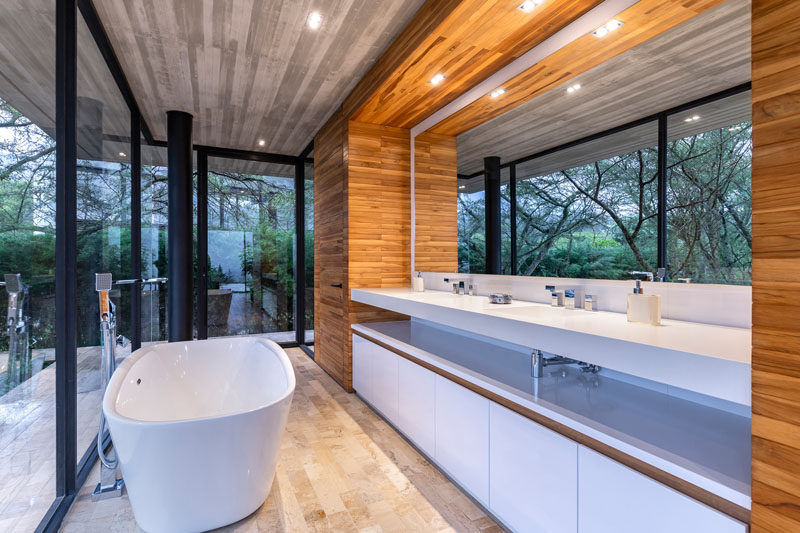 In this modern master bathroom there's a freestanding bathtub, and a long vanity with a large mirror that reflects the treetops. #MasterBathroom #BathroomDesign #ModernBathroom