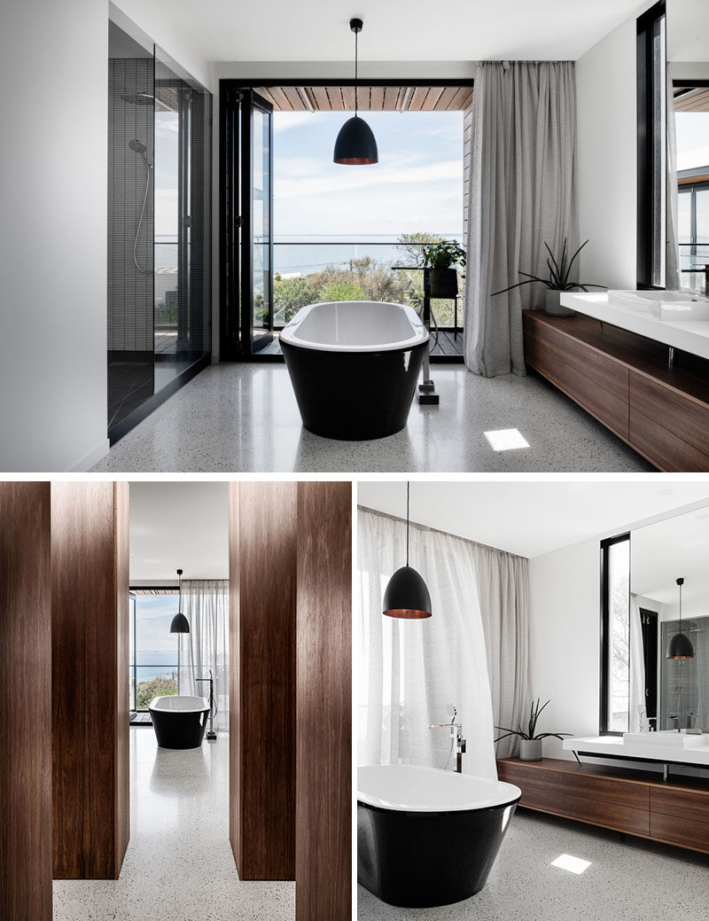 In this modern master bathroom, the freestanding bathtub has been positioned to make the most of the views, and it also separates the shower area from the vanity. #MasterBathroom #BathroomDesign
