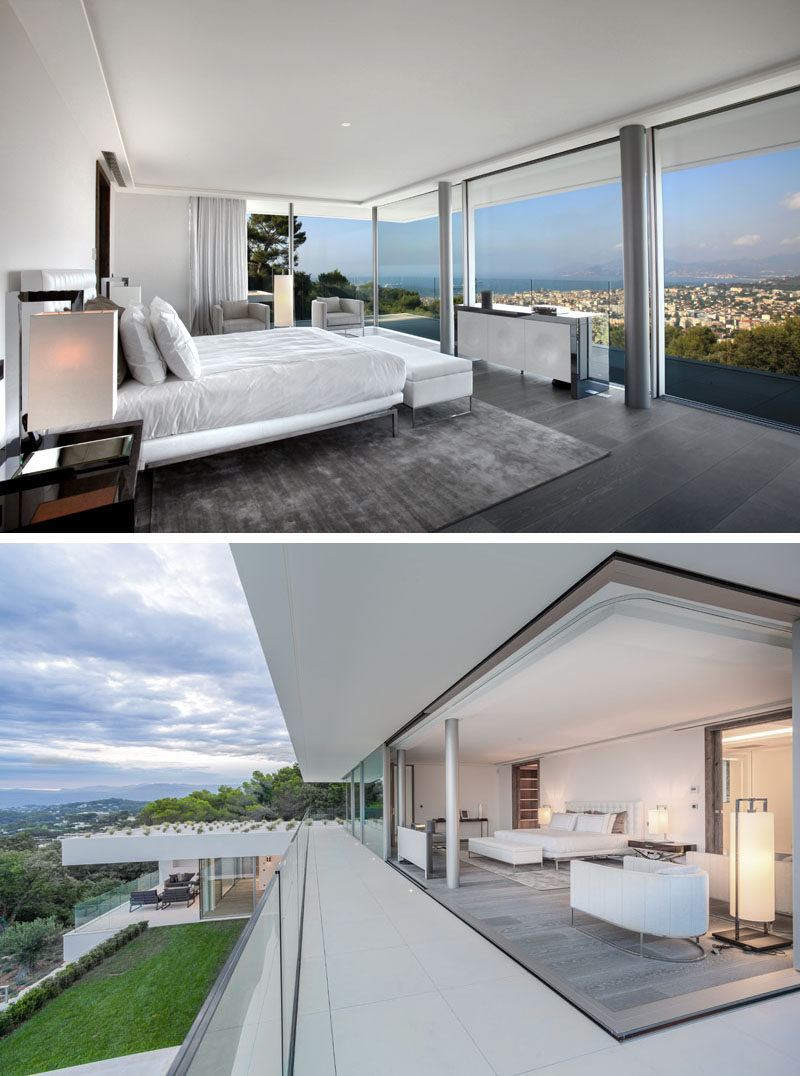 This modern master bedroom suite has minimalist window panels that slide entirely into the walls to transform the rooms into open terraces. Glass balcony railings help to create a seamless view of the surrounding area. #MasterBedroom #GlassWalls