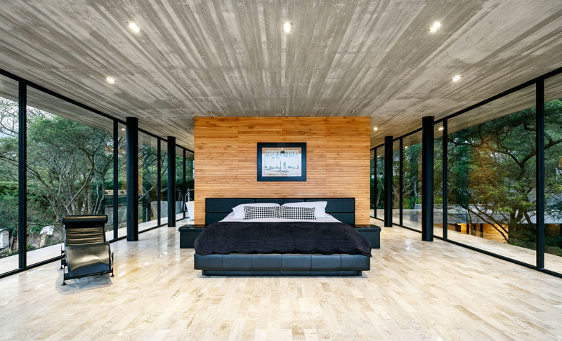 This modern master bedroom is spacious and open, and has the feeling of being in the trees due to the glass walls that surround it. #MasterBedroom #BedroomDesign #Windows