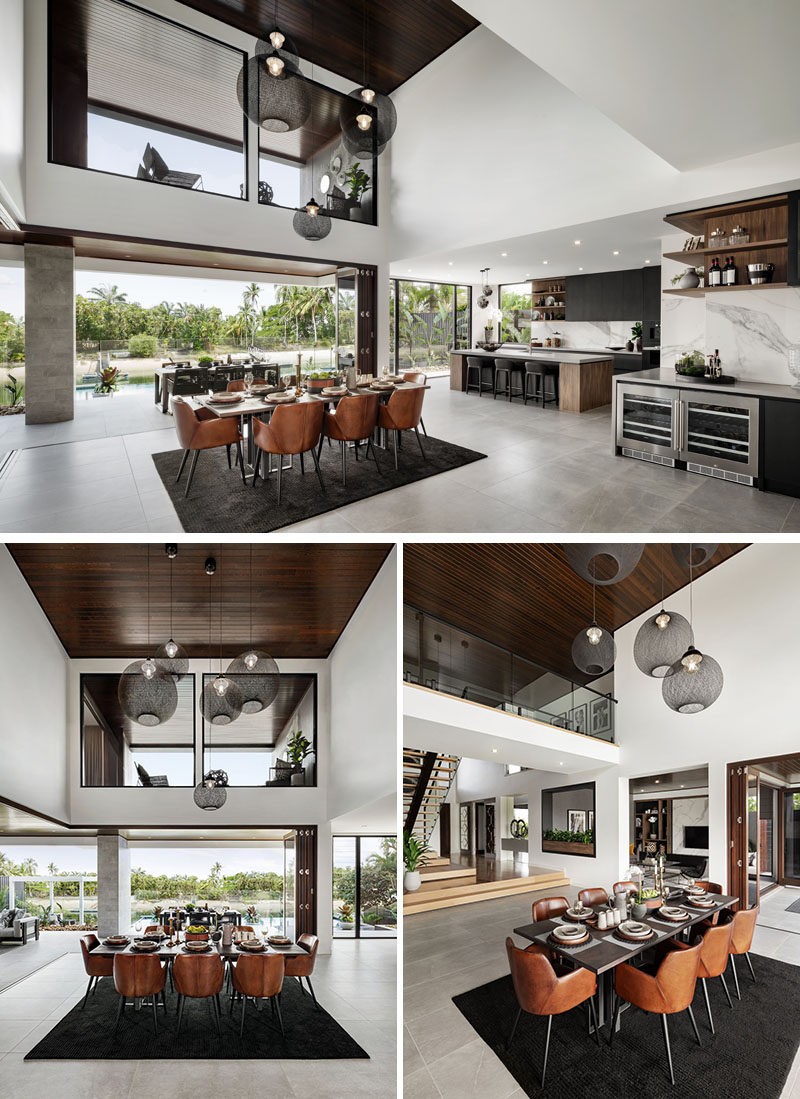 A modern dining area with a double height dark wood ceiling.